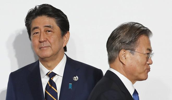 South Korean President Moon Jae-in (right) walks past Japanese Prime Minister Shinzo Abe at the G20 summit last month. Japan has not said the political issue prompted the measures. Photo: Bloomberg