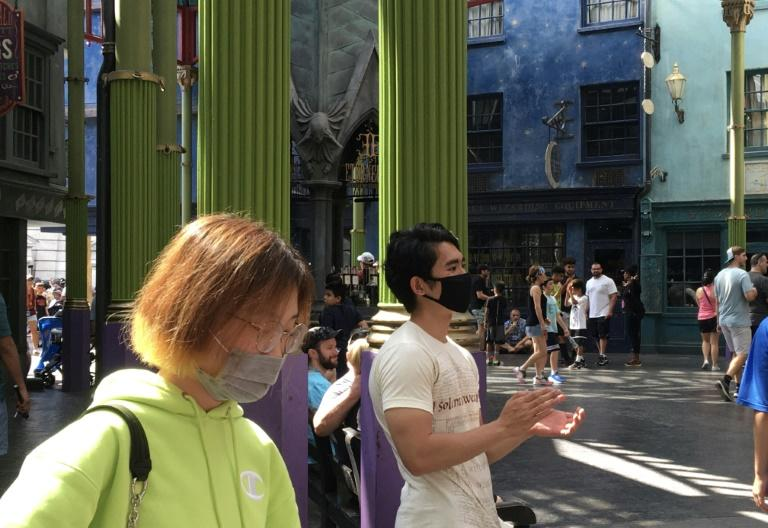 Tourists wear masks as they visit the Wizarding World of Harry Potter at the Universal Studios theme park in Orlando, Florida on March 14, 2020