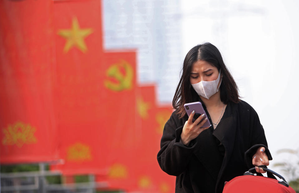 In this Jan. 23, 2021, file photo, a woman wearing face mask looks at her phone in Hanoi, Vietnam. Amnesty International has found that a hacking group known as Ocean Lotus has been staging more spyware attacks on Vietnamese human rights activists in the latest blow to freedom of speech in the communist-ruled country. (AP Photo/Hau Dinh, File)