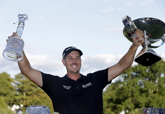 Henrik Stenson, of Sweden, celebrates with the trophies after winning the Tour Championship golf tournament and FedEx Cup at East Lake Golf Club, in Atlanta, Sunday, Sept. 22, 2013. (AP Photo/John Bazemore)