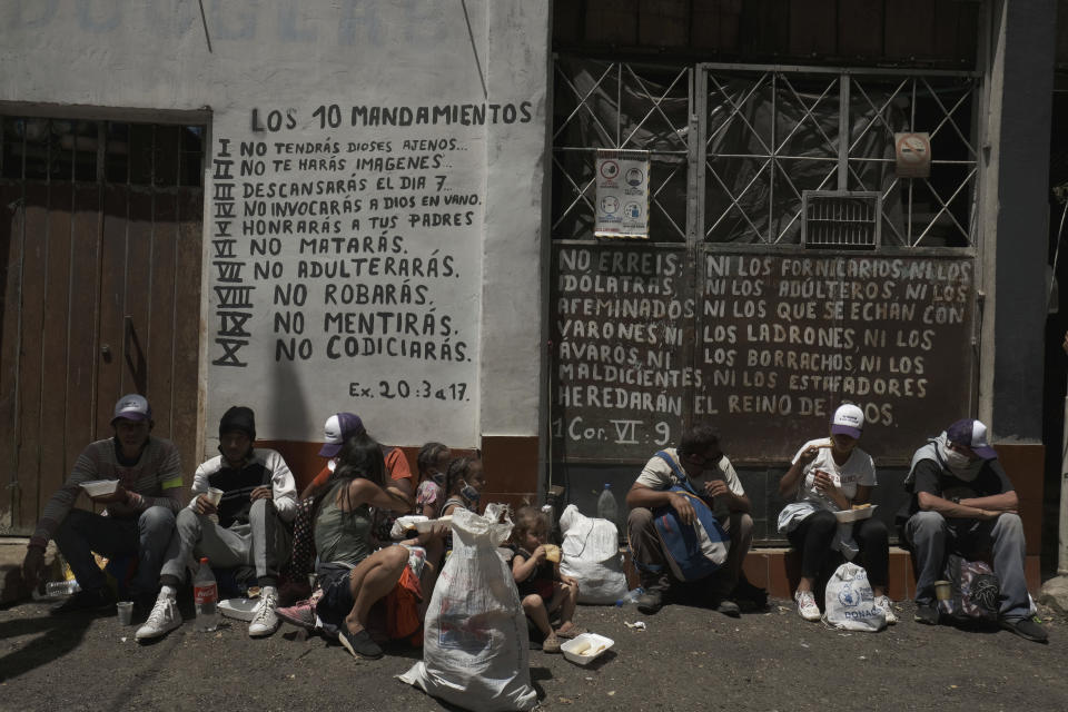 Venezuelan migrants rest as they receive free food, in front of passages from the Bible in Pamplona, Colombia, Wednesday, Oct. 7, 2020, a few hours by car from the Venezuelan border. Amid COVID-19, shelters remain closed, drivers are more reluctant to pick up hitchhikers, and locals who fear contagion are less likely to help out with food donations. (AP Photo/Ferley Ospina)