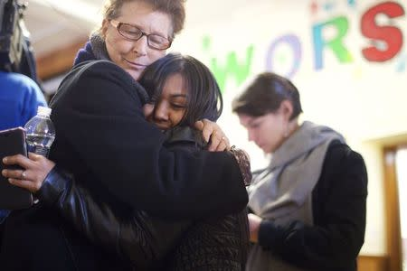 A supporter embraces Angela Navarro (C), an undocumented Honduran-born immigrant with a deportation order, who moved into West Kensington Ministry Church with her family - her husband and two U.S. born children, in Philadelphia, Pennsylvania November 18, 2014. REUTERS/Mark Makela