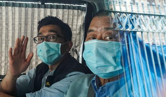 Apple Daily founder Jimmy Lai (right) is seen in custody outside the Mong Kok after his arrest on Monday. Photo: Felix Wong