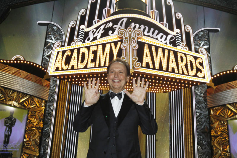 Billy Crystal pauses for a picture showing nine fingers for the number of times he's hosted the show after the 84th Academy Awards on Sunday, Feb. 26, 2012, in the Hollywood section of Los Angeles. (AP Photo/Chris Carlson)
