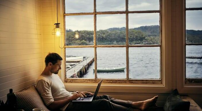 Image shows a person sitting at the window of their lakeside second home and working remotely on their laptop. SmartAsset crunched the numbers to conduct its latest study on the the hottest secondary home markets.