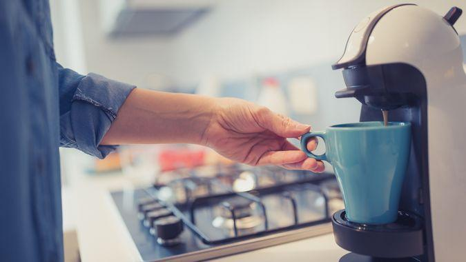Young woman is making her morning coffee in her kitchen.