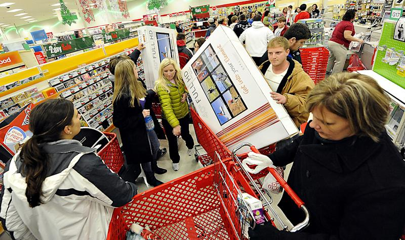 FILE - In this Nov. 25, 2011 file photo, shoppers scramble for door buster deals at Target, in Bowling Green, Ky. Americans increased their spending more slowly in March 2012, suggesting some could be worried about the economy. The Commerce Department said Monday, April 30, 2012 that consumer spending increased just 0.3 percent last month after a 0.9 percent gain in February. Income grew 0.4 percent following a 0.3 percent gain in February.  (AP Photo/Daily News, Joe Imel, File)