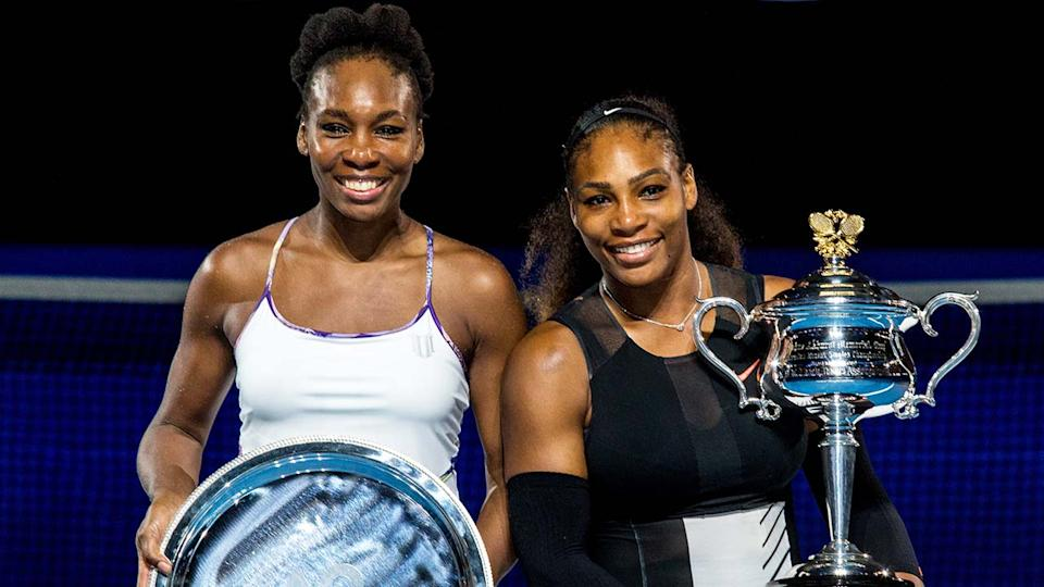 Serena Williams and Venus Williams (pictured) smile as they pose with their trophies at the Australian Open.