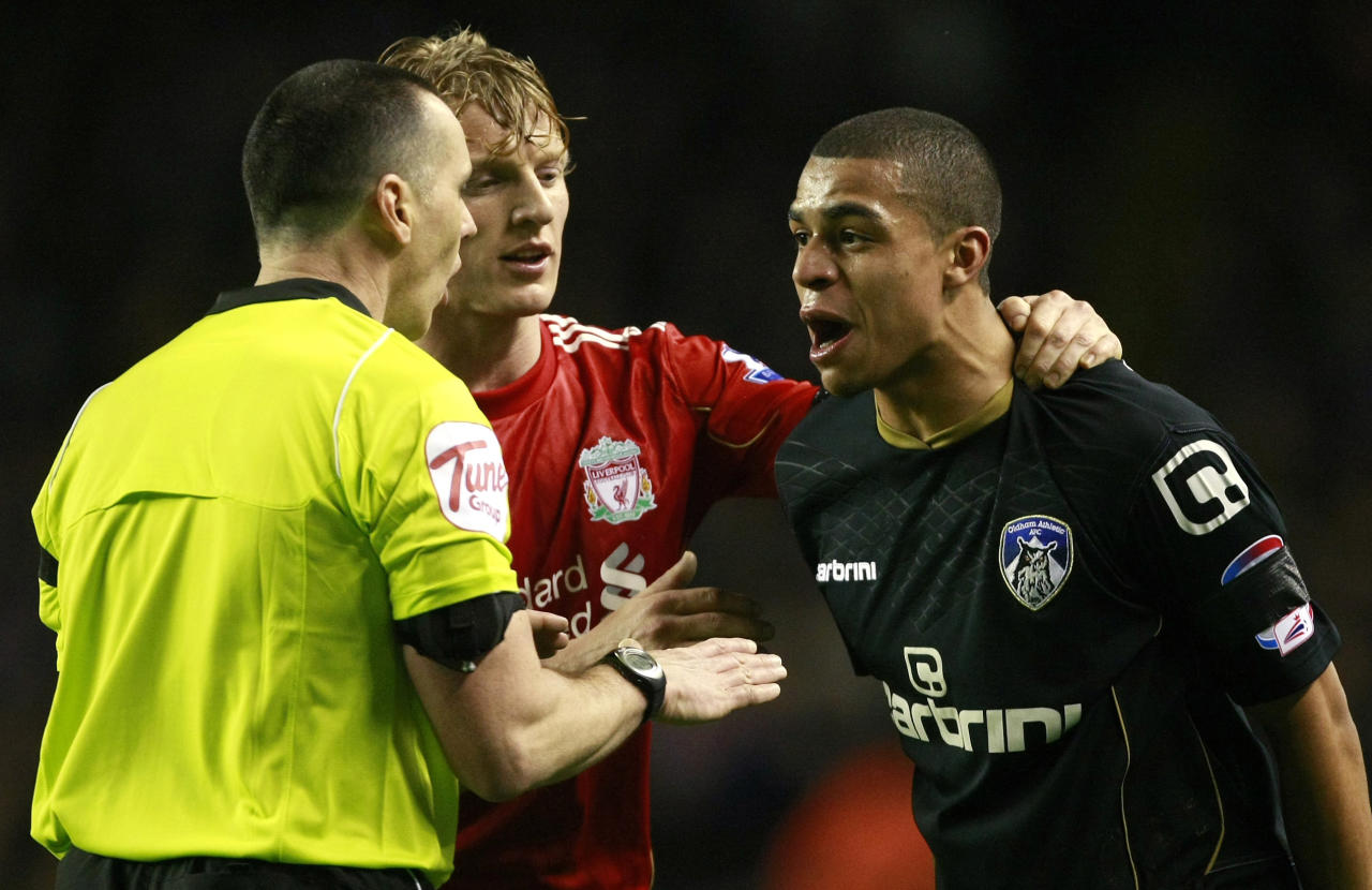 Oldham Athletic's Tom Adeyemi, right, is calmed by Liverpool's Dirk Kuyt and referee Neil Swarbrick, left, during their FA Cup third round soccer match at Anfield, Liverpool, England, Friday Jan. 6, 2012. The police are investigating an incident in which a black Oldham player appeared to be the target of abuse from Liverpool fans during an FA Cup third-round match on Friday. Oldham right back Tom Adeyemi was visibly upset late in the game at Anfield after seemingly taking offence from something shouted from the Liverpool-supporting area known as The Kop. (AP Photo/Tim Hales)