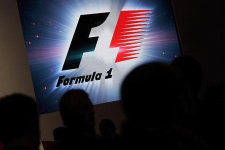 Reporters are silhouetted by a screen showing a F1 logo during a news conference to announce a Formula One race in Mexico City July 23, 2014. Mexican live events company CIE said on Tuesday it has signed a five-year contract to host Formula One races in Mexico starting in 2015. Races will be held at the Rodriguez Brothers race track in Mexico City, which last hosted a Formula One race in 1992. REUTERS/Daniel Becerril (MEXICO - Tags: SPORT MOTORSPORT F1) - GM1EA7O0ARG01