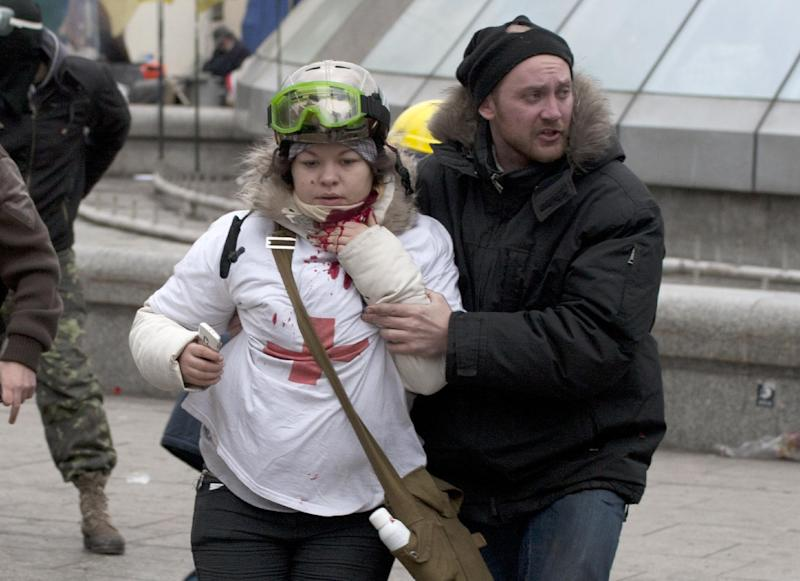 "In this Thursday, Feb. 20, 2014 photo, Olesya Zhukovska, left, is helped after being shot in her neck by a sniper bullet, in Independence Square, the epicenter of the country's current unrest, Kiev, Ukraine. ""I am dying,"" Olesya Zhukovska, a 21-year-old volunteer medic, wrote on Twitter, minutes after she got shot in the neck by a sniper's bullet as deadly clashes broke out in the center of the Ukrainian capital between protesters and police. The tweet, accompanied by a photo of her clutching her bleeding neck and being led away under fire, went viral, as social media users around the world presumed she had died and shared their grief and anger. But Zhukovska survived. She has become a symbol of the three-month protest of President Viktor Yanukovych's government and a movement for closer ties with the West and human rights. (AP Photo/Alexander Sherbakov)"