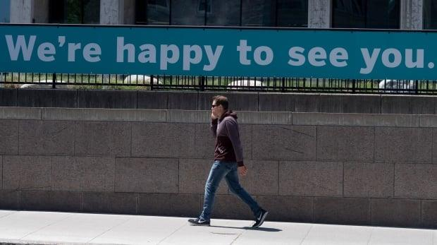 A man walks past the National Gallery of Canada in Ottawa on May 31, 2021. Despite the message on the sign behind him, the gallery and other Ontario museums are closed until the province reaches Step 3 of its reopening plan. (Adrian Wyld/Canadian Press - image credit)