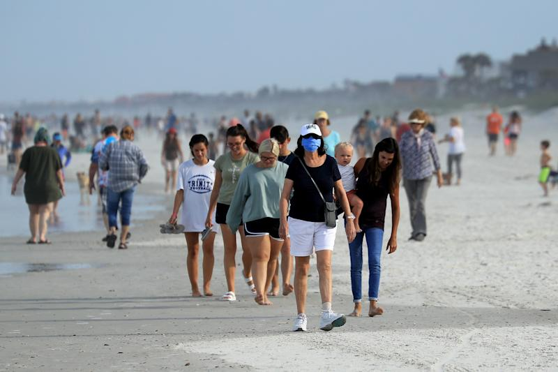 JACKSONVILLE BEACH, FLORIDA - APRIL 19: People walk down the beach on April 19, 2020 in Jacksonville Beach, Florida. Jacksonville Mayor Lenny Curry announced Thursday that Duval County's beaches would open from 7 a.m. until 11 a.m. and from 5 p.m. until 7p.m. after a decrease in coronavirus (COVID-19) cases. (Photo by Sam Greenwood/Getty Images)