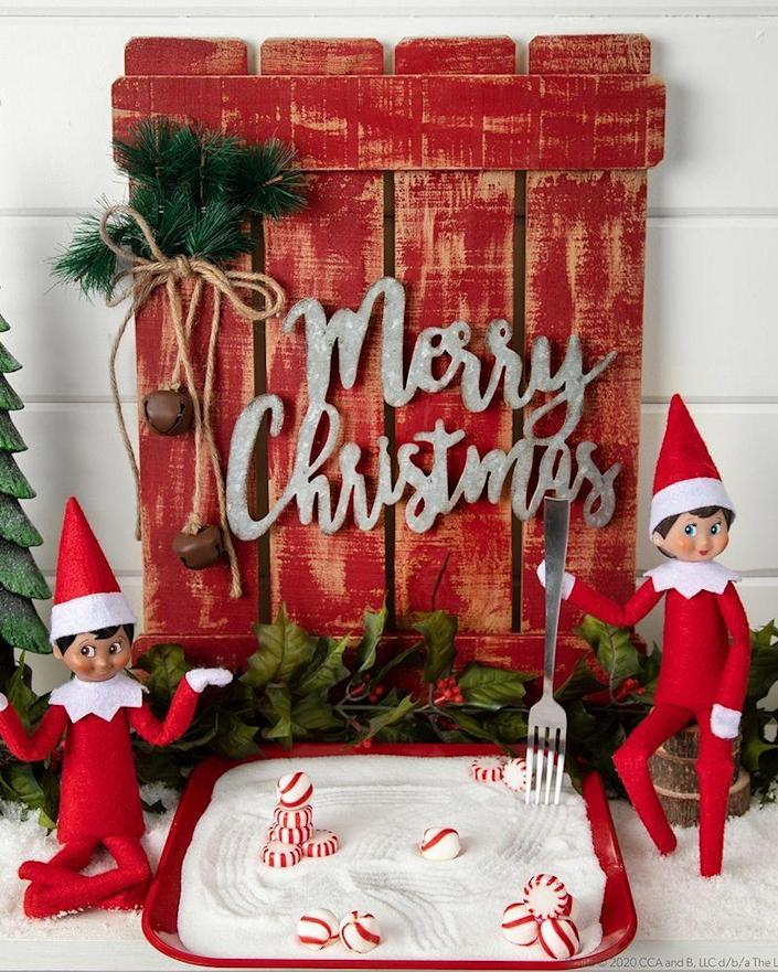 """<p>Why not let your Elves have some meditative time to themselves? A few peppermint candy """"rocks"""" and some sand, and they'll be in business.</p><p><strong>Get the tutorial at <a href=""""https://elfontheshelf.com/elf-ideas/scout-elf-zen-garden/"""" rel=""""nofollow noopener"""" target=""""_blank"""" data-ylk=""""slk:Elf on the Shelf"""" class=""""link rapid-noclick-resp"""">Elf on the Shelf</a>.</strong> </p>"""
