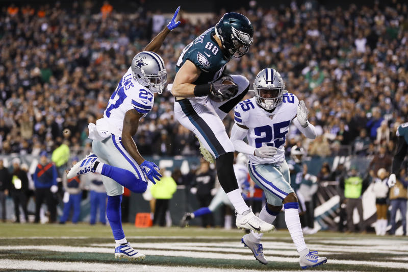 Philadelphia Eagles tight end Dallas Goedert (88) catches a touchdown pass over Dallas Cowboys cornerback Jourdan Lewis (27) and Xavier Woods (25) during the first half of an NFL football game Sunday, Dec. 22, 2019, in Philadelphia. (AP Photo/Michael Perez)