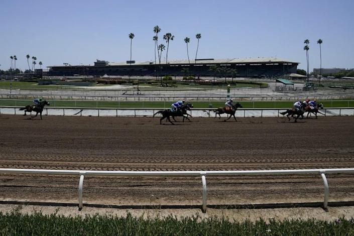 In this Friday, May 22, 2020 photo, jockeys wearing face masks ride in the first horse race past empty stands at Santa Anita Park in Arcadia, Calif. Horse racing returned to the track after being idled for one and a half months because of public health officials' concerns about the coronavirus pandemic. (AP Photo/Ashley Landis)