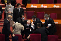 Hong Kong Chief Executive Carrie Lam, top left, watches as attendees help former Hong Kong Chief Executive Tung Chee-hwa after he fell following the opening session of China's National People's Congress (NPC) at the Great Hall of the People in Beijing, Friday, March 5, 2021. (AP Photo/Andy Wong)