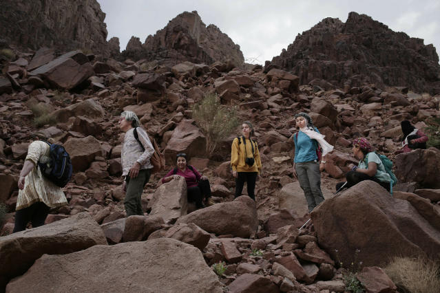 ADVANCE FOR PUBLICATION ON WEDNESDAY, APR. 10, AND THEREAFTER - In this March 29, 2019 photo, tourists trek in the mountains near Wadi Sahw, Abu Zenima, in South Sinai, Egypt. Four Bedouin women are for the first time leading tours in Egypt's Sinai Peninsula, breaking new ground in their deeply conservative community, where women almost never work outside the home or interact with outsiders. The women guide groups of female tourists through the stunning mountain landscapes, part of a Bedouin-led project of hiking tours. (AP Photo/Nariman El-Mofty)