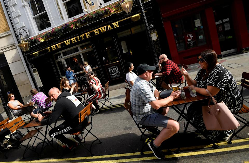 People drink outside a pub at the Covent Garden shopping and dining district, amid the spread of the coronavirus disease: Reuters