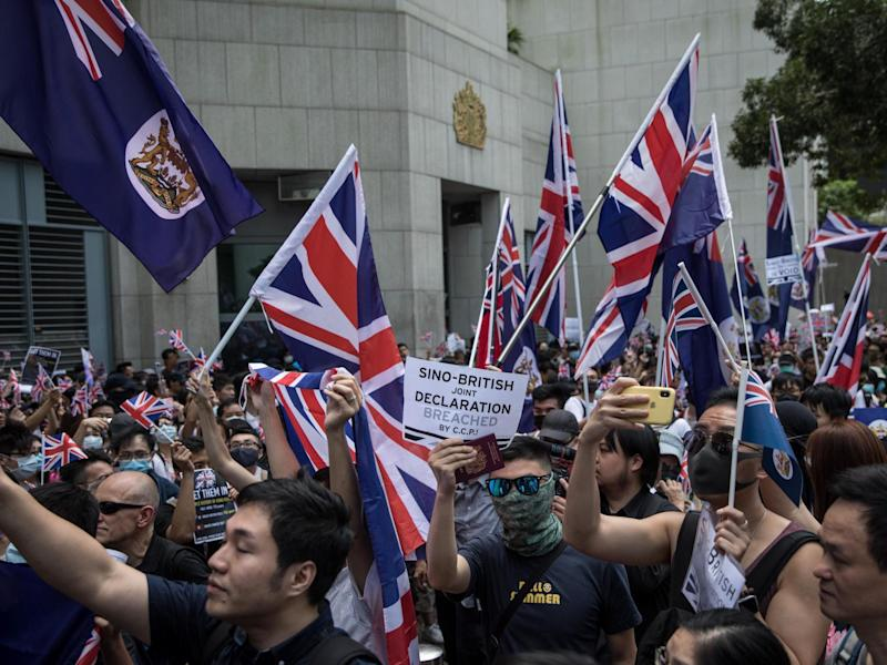 Pro-democracy protesters wave flags and chant slogans outside the UK embassy: Getty Images