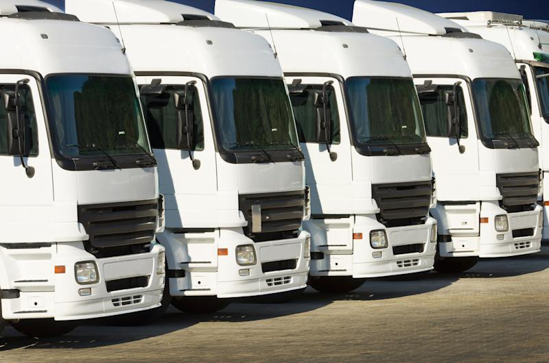 A row of white commercial heavy trucks parked side by side.