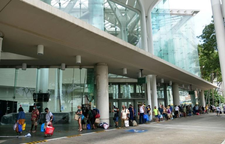 People line up to shelter at the Hawaii Convention Center, seeking a safe place to weather Hurricane Douglas in Honolulu, Hawaii, on July 26, 2020