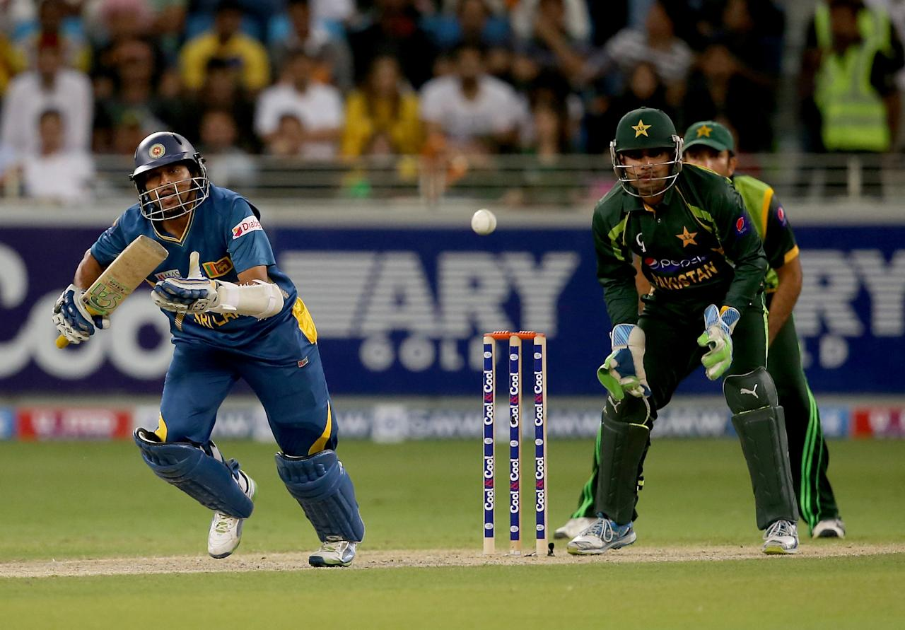 DUBAI, UNITED ARAB EMIRATES - DECEMBER 20:  TM Dilshan of Sri Lanka bats as Umar Akmal of Pakistan looks on during the second One-Day International (ODI ) match between Sri Lanka and Pakistan at the Dubai Sports City Cricket Stadium on December 20, 2013 in Dubai, United Arab Emirates.  (Photo by Francois Nel/Getty Images)