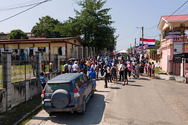 People queue outside a polling station to cast their vote during the election for a new prime minister, in Belmopan