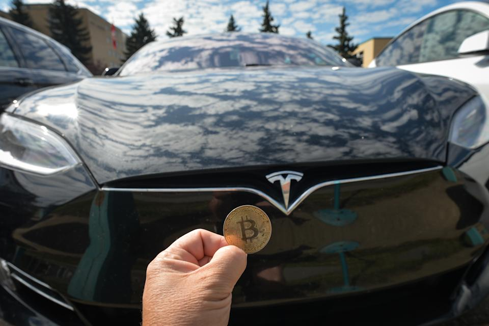 Illustrative image of a commemorative bitcoin seen in front of the Tesla car. Thursday, August 26, 2021, in Edmonton, Alberta, Canada. (Photo by Artur Widak/NurPhoto via Getty Images)
