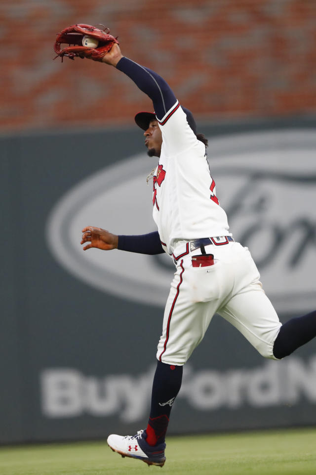 Atlanta Braves second baseman Ozzie Albies (1) hauls in a fly ball from New York Mets third baseman J.D. Davis (28) in the third inning of a baseball game Tuesday, Aug. 13, 2019, in Atlanta. (AP Photo/John Bazemore)