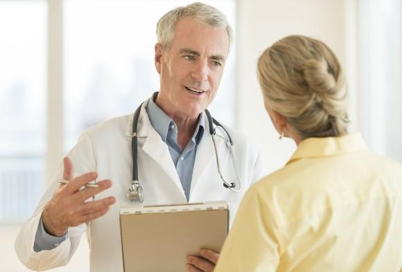A doctor with a clipboard having a discussion with a patient.