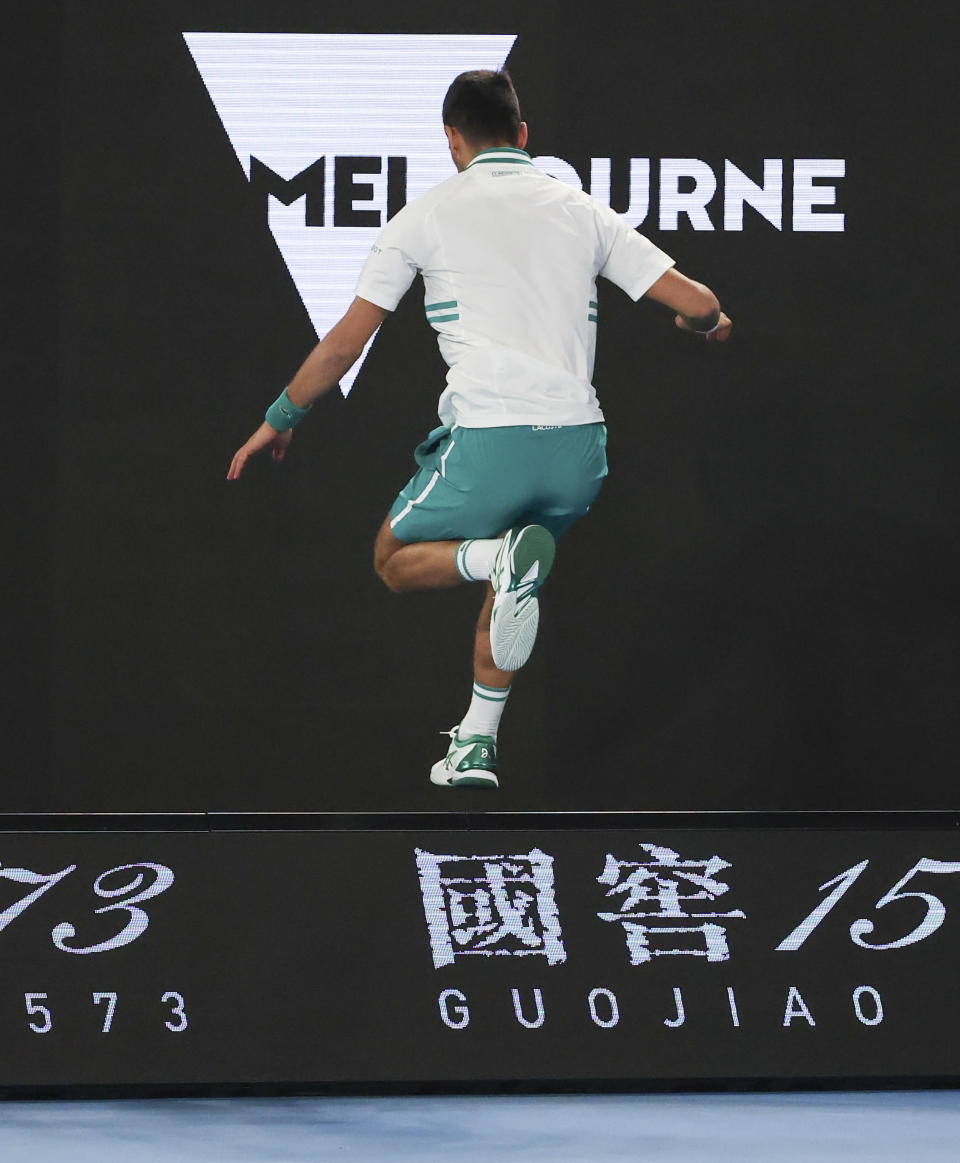 Serbia's Novak Djokovic leaps a signboard as he attempts to hit a return to Canada's Milos Raonic during their fourth round match at the Australian Open tennis championship in Melbourne, Australia, Sunday, Feb. 14, 2021.(AP Photo/Hamish Blair)