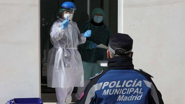 PHOTO: A health worker gestures to a municipal police officer during tests for the coronavirus in Madrid, March 25, 2020.  (Rafa Albarran/Madrid City Hall/AFP/Getty Images)