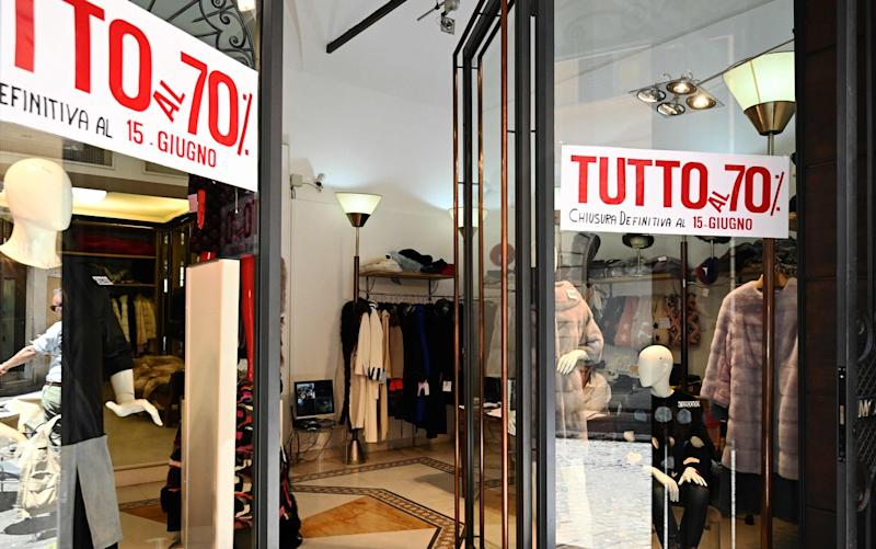 """A view shows a women's clothing shop, on which placards read """"Everything at 70 percent, final closure on June 15"""" - AFP"""