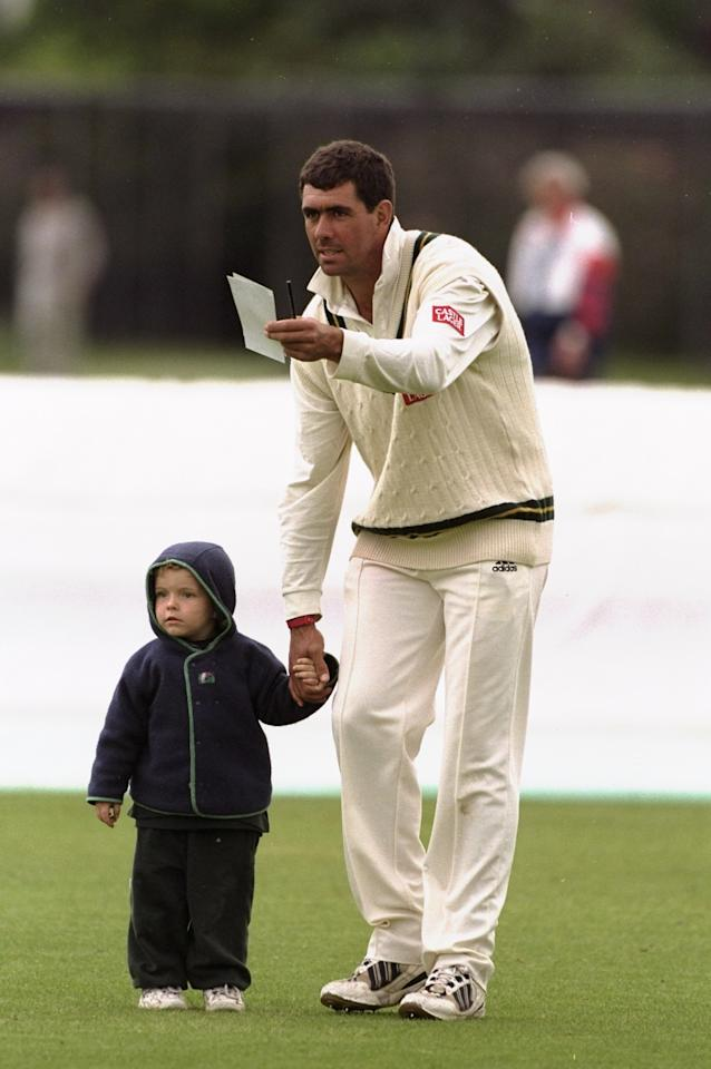 26 Jun 1998:  Hansie Cronje of South Africa holds the hand of a young fan during a tour match against British Universities at Fenners in Cambridge, England. \ Mandatory Credit: Craig  Prentis/Allsport