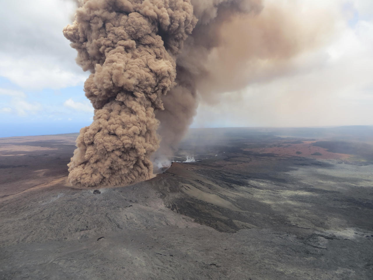 FILE - This May 4, 2018 file aerial image released by the U.S. Geological Survey shows a column of robust, reddish-brown ash plume that occurred after an earthquake shook the Big Island of Hawaii. White plumes of acid and extremely fine shards of glass billowed into the sky over Hawaii as molten rock from Kilauea volcano poured into the ocean, creating yet another hazard from an eruption that began more than two weeks ago; a toxic steam cloud. (U.S. Geological Survey via AP, file)