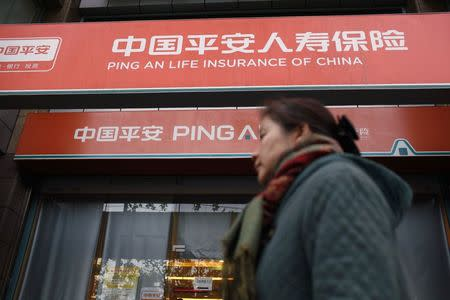 A woman walks past a Ping An Insurance building in Shanghai in this December 6, 2012 file photo. REUTERS/Aly Song
