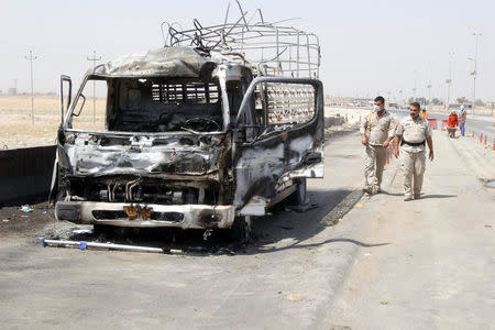 Policemen inspect a burnt-out vehicle at the site of a bomb attack at a checkpoint in the city of Kirkuk