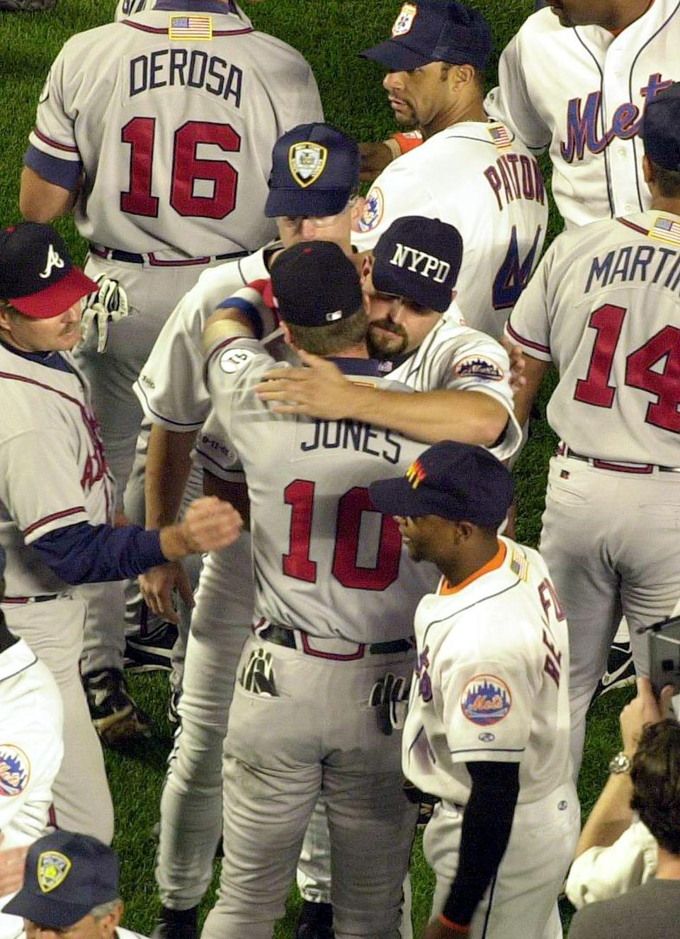 New York Mets pitcher Rick White, wearing an NYPD cap, embraces Atlanta Braves third baseman Chipper Jones before the start of the Sept. 21, 2001, game at Shea Stadium.