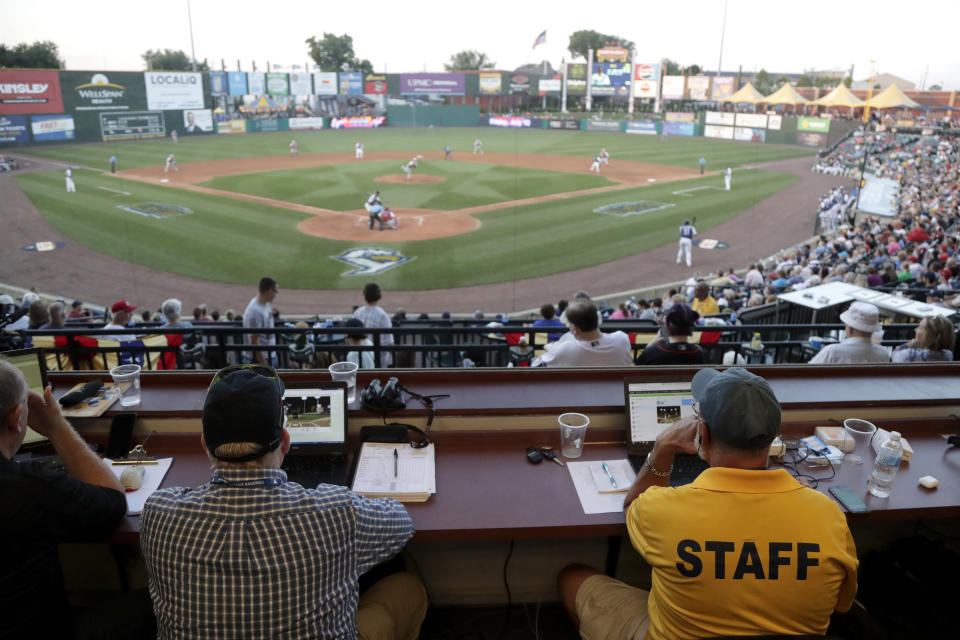 FILE - In this July 10, 2019, file photo, Ron Besaw, right, operates a laptop computer as home plate umpire Brian deBrauwere gets signals from radar with the ball and strikes calls during the fourth inning of the Atlantic League All-Star minor league baseball game in York, Pa. Computer umpires for balls and strikes are coming to a low-level minor league but are a while away from the big leagues. Major League Baseball plans to use Automated Ball-Strike technology (ABS) in eight of nine ballparks at the Low-A Southeast League, which starts play May 4 across Florida. (AP Photo/Julio Cortez, File)