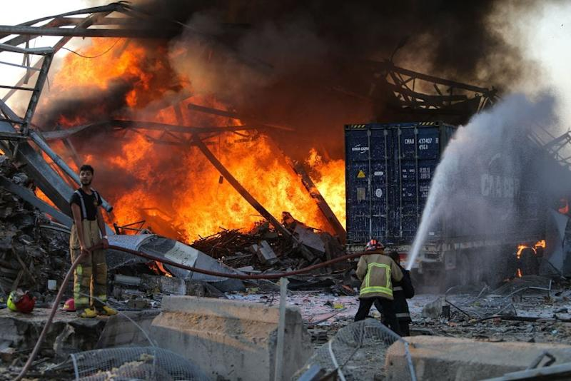 Firefighter douse a blaze at the scene of an explosion at the port of Lebanon's capital Beirut on August 4, 2020.