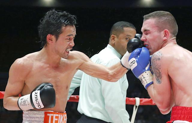 Japanese champion Shinsuke Yamanaka, left, hits his left on the face of Belgian challenger Stephane Jamoye in the seventh round in their WBC bantamweight boxing title bout in Osaka, western Japan, Wednesday, April 23, 2014. Yamanaka defended his title with a technical knockout in the ninth round. (AP Photo/Kyodo News)