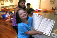 Lily Osgood, 7, who has Down syndrome, shows off her completed work with her mother, Jennifer, and brother, Noah, 12, at their home, Tuesday, July 20, 2021, in Fairfax, Vt. For some families, the switch to homeschooling was influenced by their children's special needs. Having observed Lily's progress with reading and arithmetic while at home during the pandemic, Jennifer is convinced homeschooling is the best option for her going forward. (AP Photo/Charles Krupa)