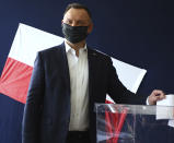 Poland's President Andrzej Duda casts his vote during presidential election in Krakow, Poland, on Sunday June 28, 2020. The election will test the popularity of incumbent President Andrzej Duda who is seeking a second term and of the conservative ruling party that backs him. (AP Photo/Beata Zawrzal)