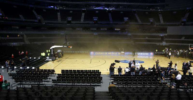 Smoke engulfs basketball court of The Mexico City arena during a regular season NBA match between the Timberwolves and the San Antonio Spurs in Mexico City, Wednesday, Dec. 4, 2013. NBA spokeswoman Sharon Lima says the smoke was coming from a generator fire outside the arena. There was no word yet if the start of the game will be delayed. (AP Photo/Eduardo Verdugo)
