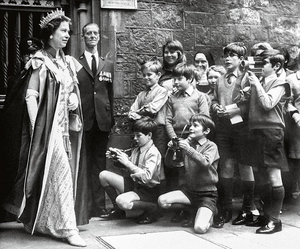 The Queen is photographed by boys of the Westminster Abbey choir school as she leaves the Abbey after a service for the Order. 1972. (Heritage-Images/TopFoto)