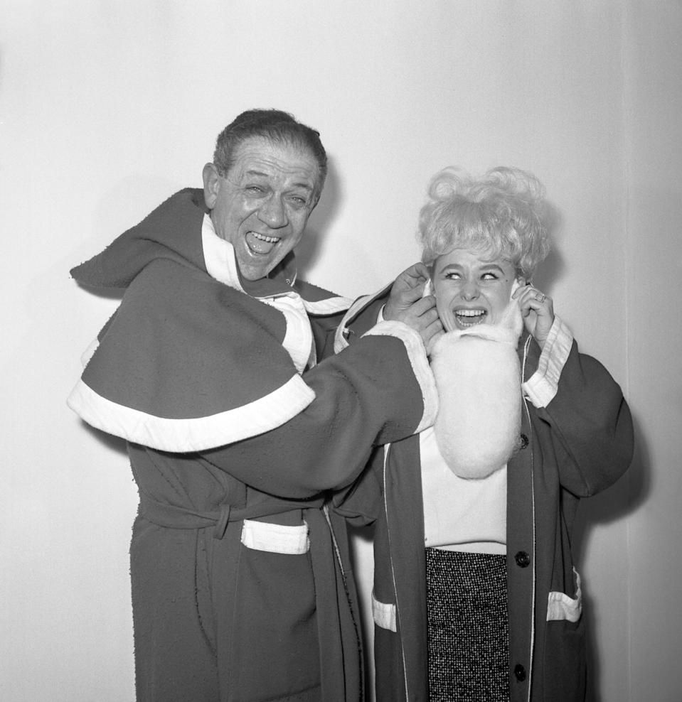 Barbara Windsor, ably assisted by comedian Sid James, is dressing up for her role as Father Christmas at the Variety Club luncheon at the Savoy Hotel, London.