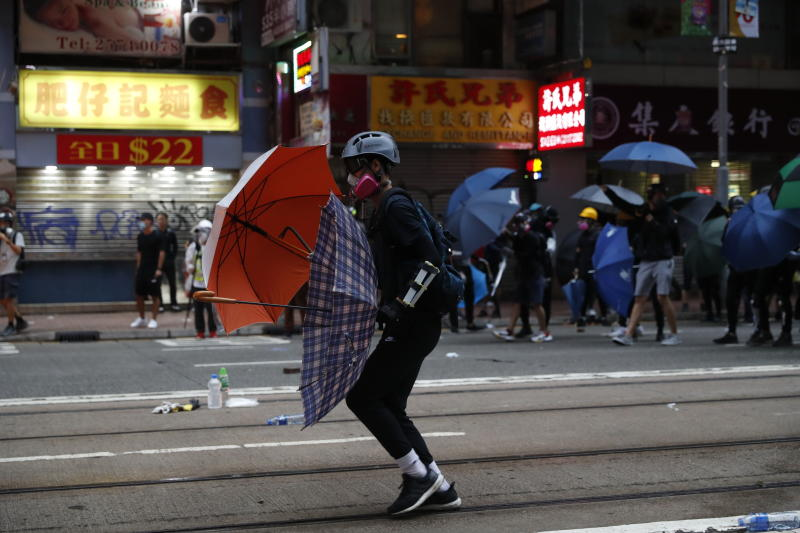 "In this Oct. 6, 2019, photo, protestors clash with police in Hong Kong. Shouting ""Wearing mask is not a crime,"" tens of thousands of protesters braved the rain Sunday to march in central Hong Kong as a court rejected a second legal attempt to block a mask ban aimed at quashing violence during four months of pro-democracy rallies. (AP Photo/Vincent Thian, File)"