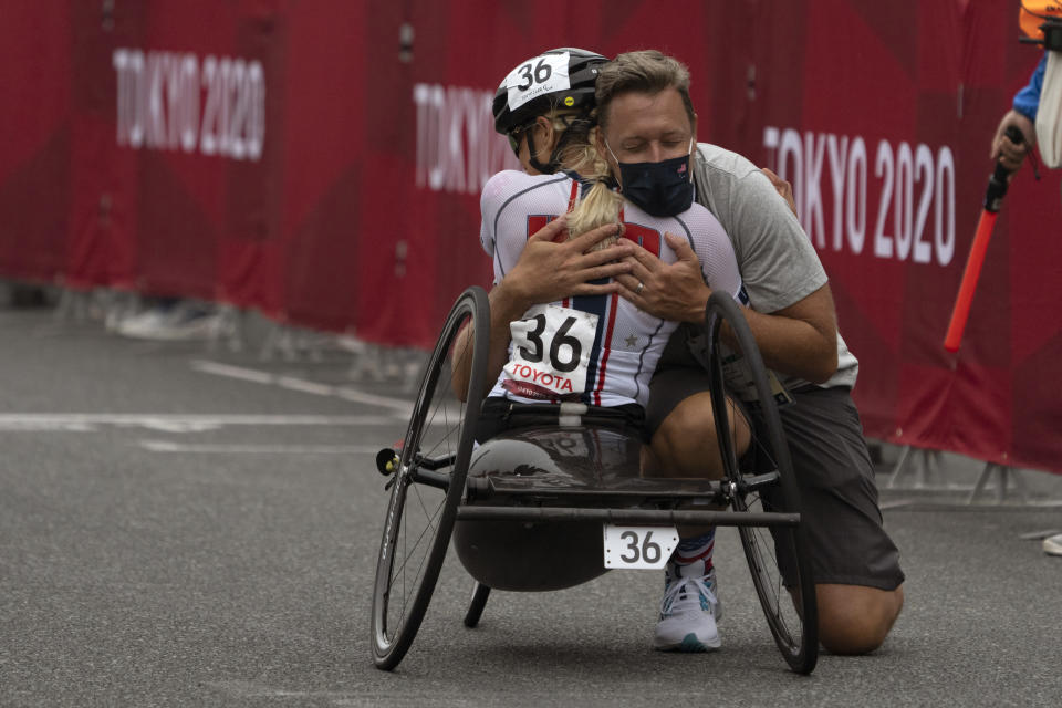 Oksana Masters, from USA, celebrates with a team member after wining at Women's H5 Road Race at the Fuji International Speedway at the Tokyo 2020 Paralympic Games, Wednesday, Sept. 1, 2021, in Tokyo, Japan. (AP Photo/Emilio Morenatti)