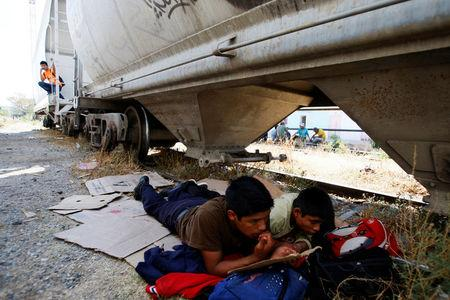 Central American migrants rest next to the train tracks while waiting for a freight train to travel to north Mexico to reach and cross the U.S. border, at Arriaga